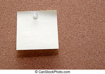Blank  post it note stuck on brown cork board