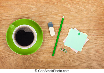 Blank post-it with office supplies and coffee cup on wooden...