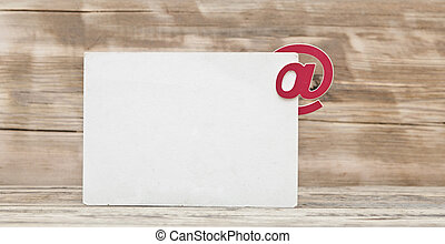 blank postcard and E-mail symbol on old wooden background. concept of E-Mail