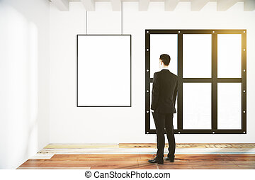 Blank poster on white wall in empty room with wooden floor and businessman, mock up