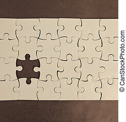 blank puzzle with missing piece, on a brown background.