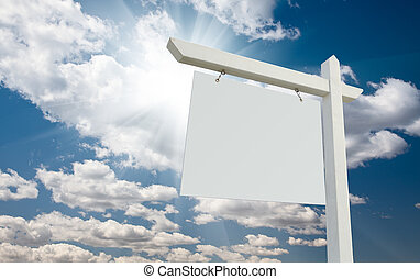 Blank Real Estate Sign over Clouds and Blue Sky