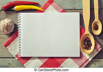 Blank recipe book with kitchen towel on wooden background
