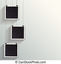 Blank retro vintage photo frames on a wall.