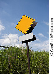 Blank road warning sign against blue sky
