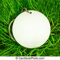 Blank round badge in green grass