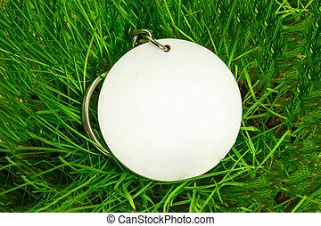 Blank round badge in green grass