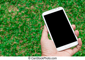 blank screen mobile phone in hand on green grass