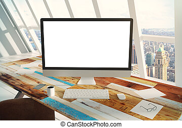 Blank screen of computer on a wooden table in the  office