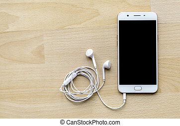Blank screen smartphone with earphone on wooden table Top corner