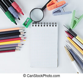blank sheet of Notepad and office supplies on white background