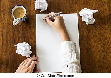 Blank sheet of paper and pen on bright wooden office desk with hands of a person