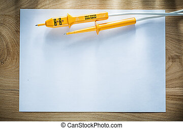Blank sheet of paper electrical tester on wooden board