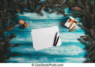 Blank sheet of paper on a blue wooden table with Christmas items.