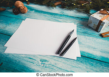 Blank sheet of paper on Christmas blue wooden table.