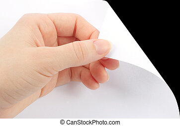 Blank sheet of paper with hand on black background close-up