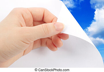 Blank sheet of paper with hand on sky background close-up