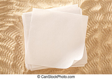 Blank sheets of paper on sand