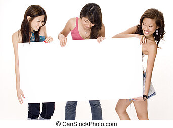 Blank Sign #2 - Three attractive young women look at the big...