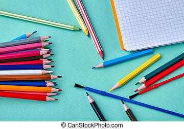 Blank sketchbook and scattered pencils on color background.