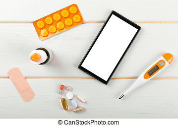 blank smartphone with medical items on the desk. top view