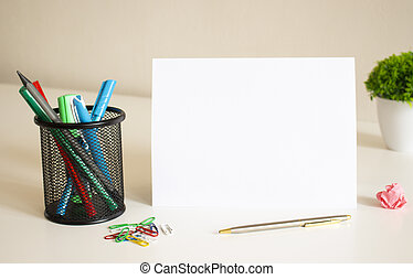 Blank space for inscription on a white folded sheet of paper on the table. Nearby are pens and pencils.
