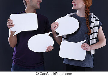 Blank speech bubbles - Man and woman holding blank speech...