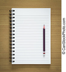 blank spiral notepad and pencil on wood background