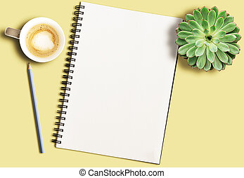 spiral notepad on yellow desk with pencil, potted succulent plant and coffee mug