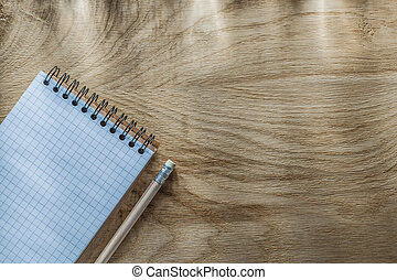 Blank spiral notepad pencil on wooden board top view