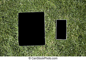 blank tablet and phone on grass