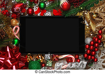 Blank tablet surrounded with Christmas decorations
