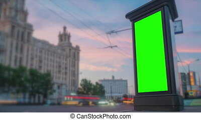 Timelapse - blank vertical street green billboard poster or advertising pillar and fast moving car at evening. Consumerism, time lapse, green screen, template, mock up, copyspace, chroma key concept