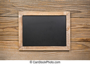 Blank vintage chalkboard with distressed frame on a wooden background