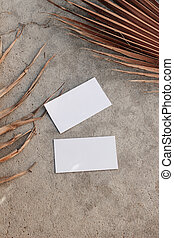 Blank white business cards mockups and dry brown palm leaves...