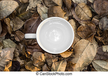 Blank white coffee cup on dry leaves.