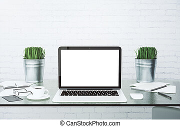 Blank white laptop screen on glassy table with cup of coffee at brick wall background, mock up