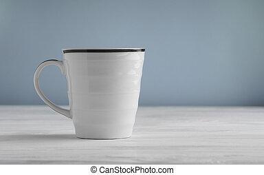 Blank white mug mock up on white wooden table and blue background