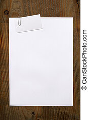 blank white paper and business card clipped a paperclip on woode