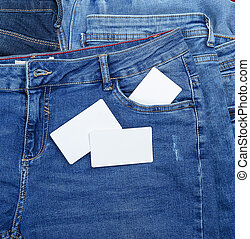 blank white paper business cards on a blue jeans
