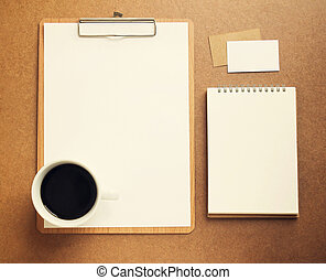 Blank white paper on clipboard and notebook with cup of coffee,