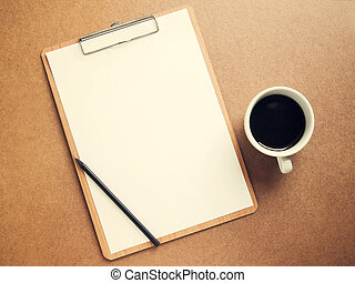 Blank white paper on clipboard with cup of coffee, retro filter