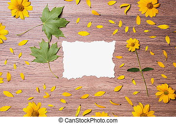 Blank white paper on the wooden background. The composition of yellow flowers, petals and baked decorative cards. Work place designer. The space for the text.