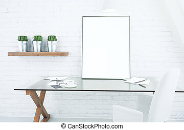 Blank white picture frame on glassy table in modern loft ...
