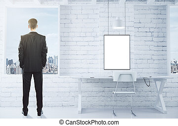 Blank white picture frame on white brick wall and businessman looking out the window in loft room, mock up