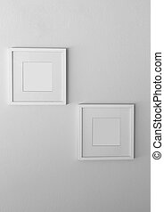 Blank white picture frame on white wall