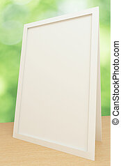 Blank white picture frame on wooden table, mock up