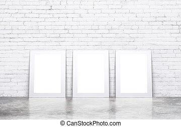 Blank white picture frames on concrete floor in empty loft room with white brick wall, mock up