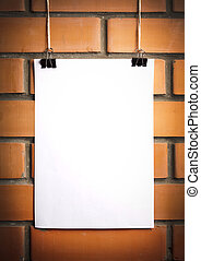 Blank white poster on a rope, brick wall on the background