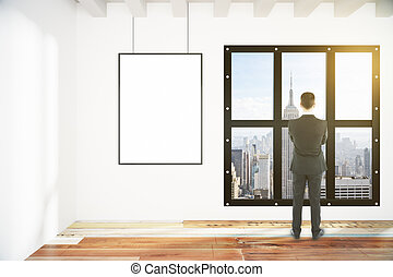 Blank white poster on white wall and businessman in empty loft room with city view, mock up
